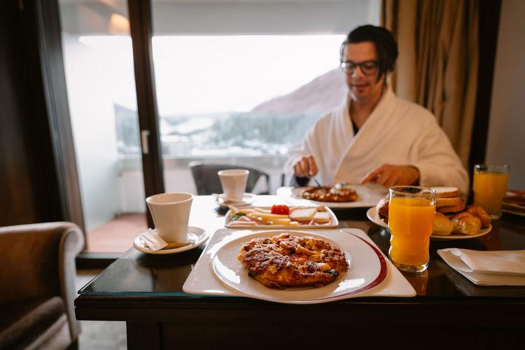 View of man in bathrobe sitting and having breakfast in room