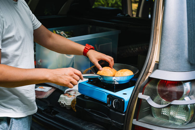 Midsection of man preparing food on camping stove in car trunk