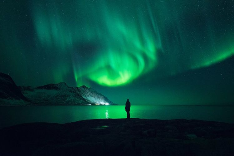 Man standing on mountain against sky at night during winter