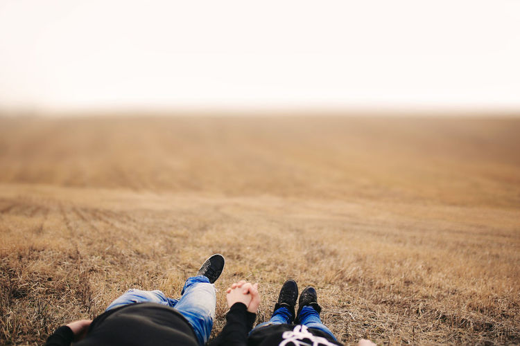Low section of couple holding hands while relaxing at field
