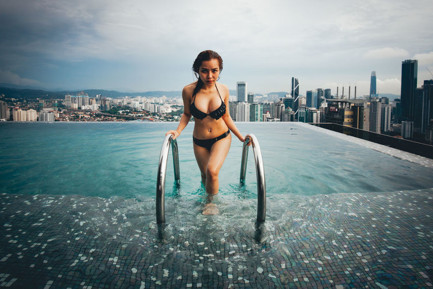 Building Exterior Young Adult City One Person Architecture Water Built Structure Full Length Cityscape Young Women Sky Beautiful Woman Bikini Swimwear Clothing Nature Real People Women Swimming Pool Hair Outdoors Office Building Exterior Skyscraper Hairstyle Cityscape
