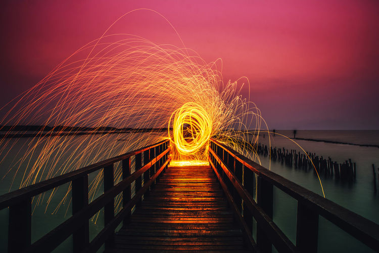 Railing Sky Water Illuminated Wire Wool Motion Spinning Long Exposure Nature Bridge Blurred Motion Footbridge Night Glowing Orange Color Connection Architecture Built Structure Sunset Bridge - Man Made Structure Outdoors Diminishing Perspective Sparks