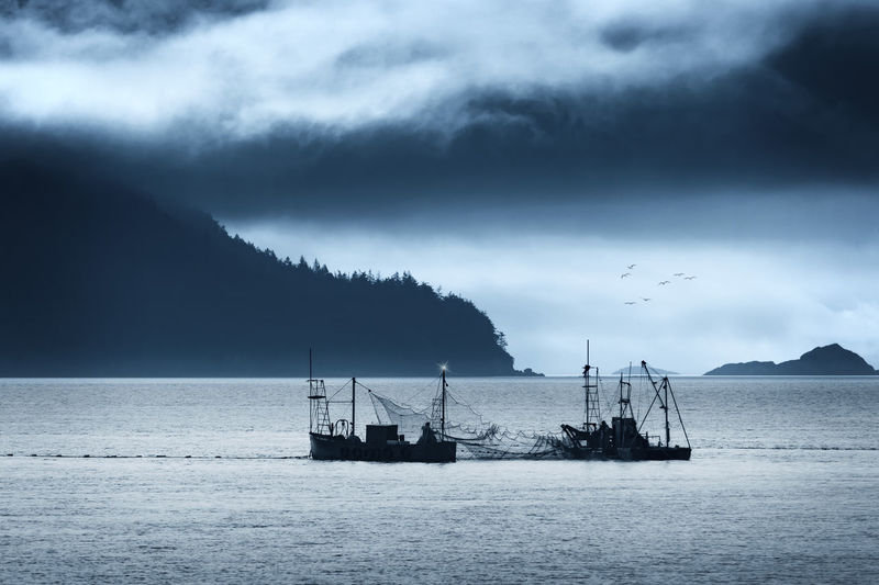 Silhouette Fishing Boats In Sea Against Cloudy Sky