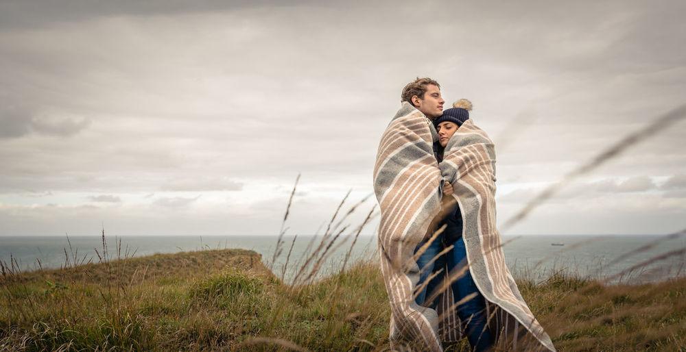 Couple Covered With Blanket Standing By Sea On Field