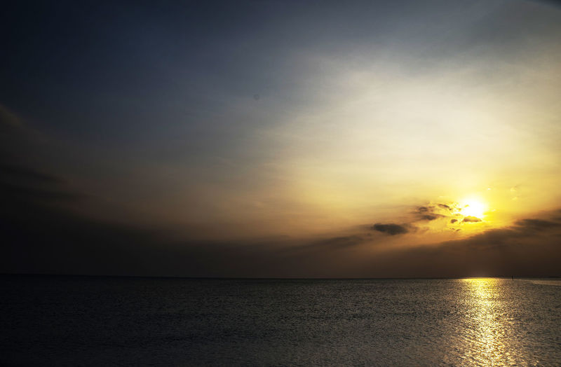 As the sun goes down its light reflects in the sea Calmness Golden Low Light Sunlight Beauty In Nature Blue Clouds And Sky Evening Good Night Idyllic Nature Nightfall No People Ocean Outdoors Reflection Scenics Sea Sky Sun Sundown Sunset Tranquil Scene Tranquility Water