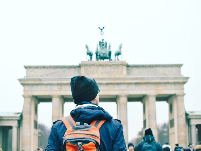 Rear view of man looking at brandenburg gate in city against clear sky