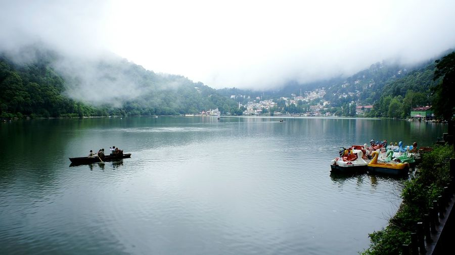 Side View Of Boating In Calm Lake Against Plants