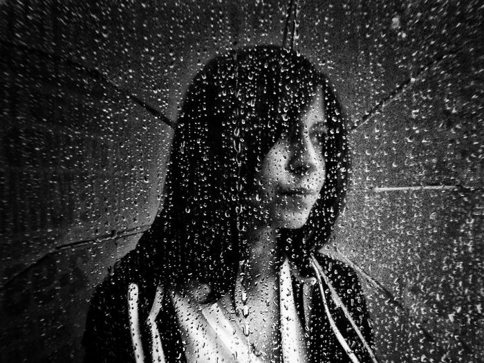 Thoughtful Young Woman With Umbrella Behind Wet Glass During Rainy Day