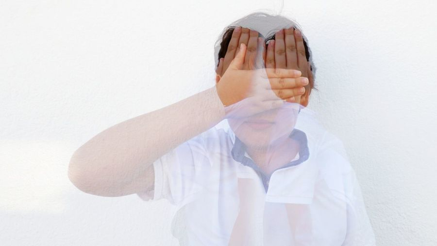 Double Exposure Of Boy Covering Face Against White Background