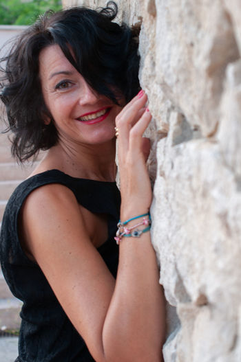 Portrait of woman smiling while standing by wall