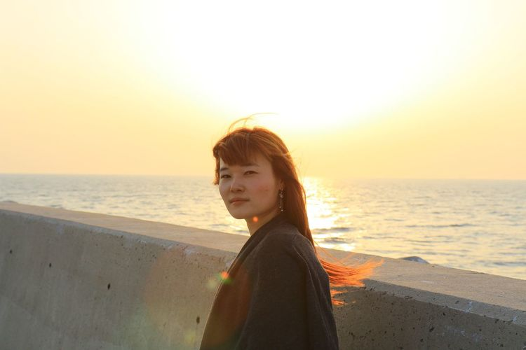 Portrait of young woman standing by retaining wall against sea during sunset