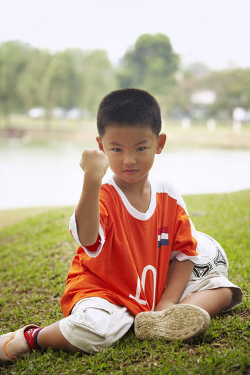 Full Length Portrait Of Confident Boy With Soccer Ball Gesturing On Field At Park