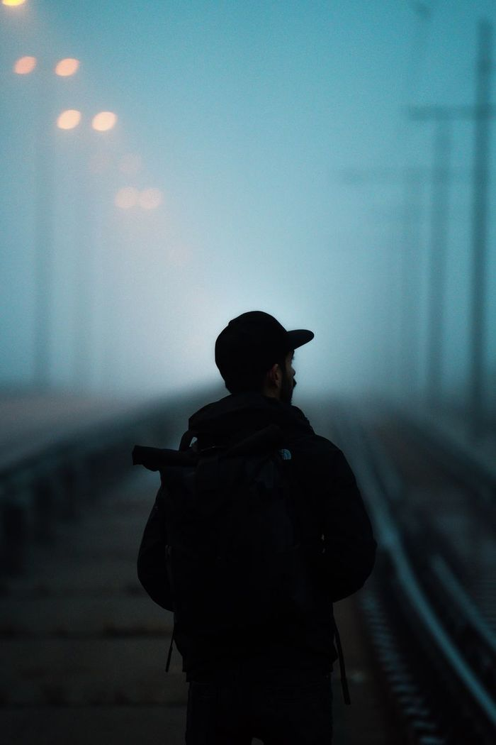 REAR VIEW OF MAN STANDING BY RAILROAD TRACKS AGAINST SKY