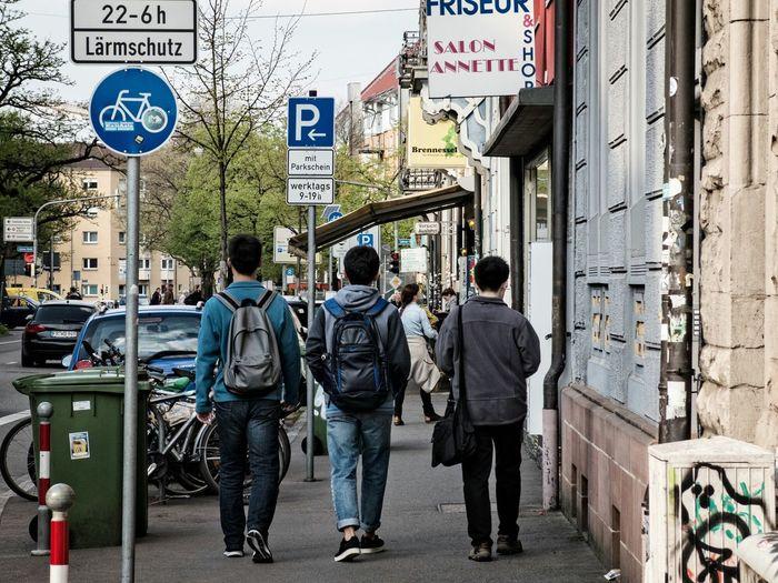 Rear view full length of man walking on sidewalk