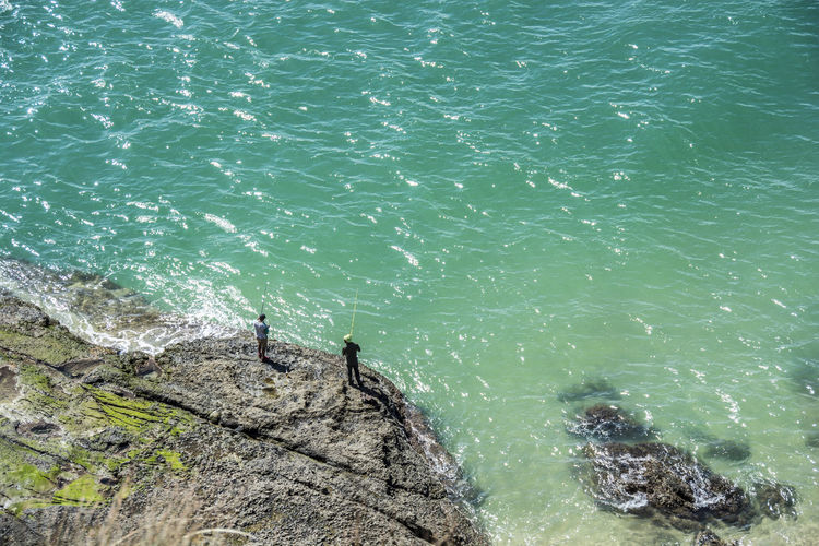 High Angle View Of Men Fishing By Turquoise Sea