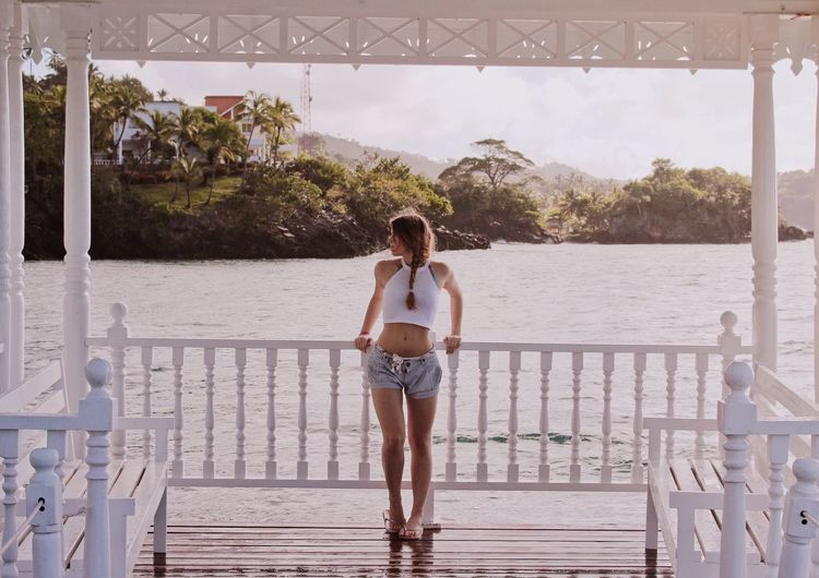 Full Length Of Young Woman Standing On Pier Over Lake
