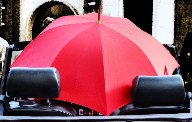 Red Umbrella In Convertible Car
