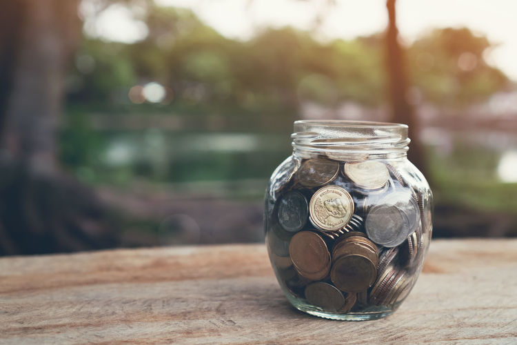 Coins in the bottle, Money growing concept and the goal success. Focus On Foreground Jar Table No People Finance Close-up Day Glass - Material Coin Transparent Wood - Material Nature Container Outdoors Savings Business Plant Wealth Front Or Back Yard Still Life