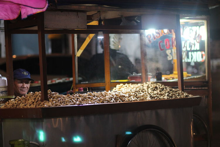 Male vendor selling peanuts at market stall during night