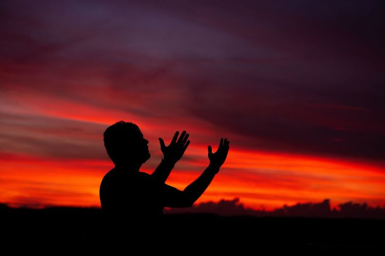 Silhouette man with arms raised against orange sky