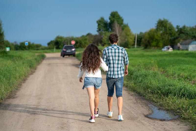 Rear view of friends walking on road