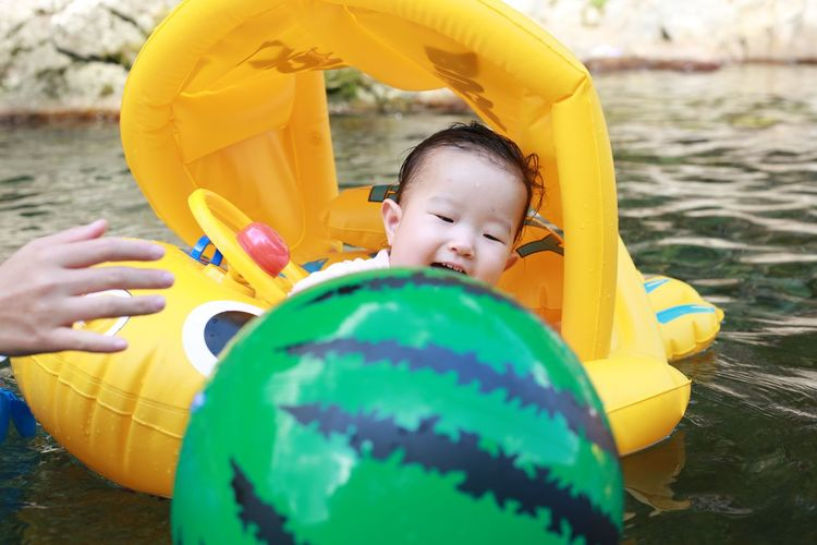 Baby girl on inflatable ring in pond