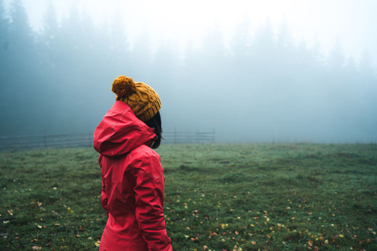 Rear view of woman standing on field during foggy weather