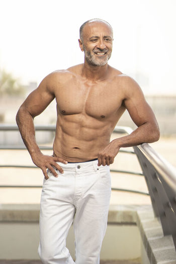 Portrait of shirtless man standing against blurred background