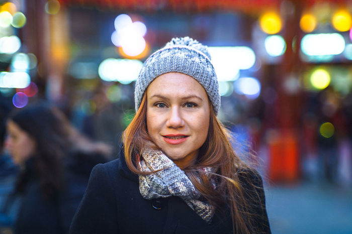 Auburn Chinatown Bobble Hat  Bokeh Close-up Focus On Foreground Front View Grey Cap Happiness Head And Shoulders Headshot Leisure Activity Lifestyles Looking At Camera One Person Outdoors Portrait Real People Warm Clothing Young Adult Young Women