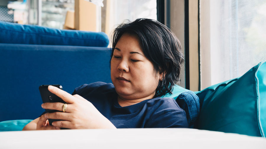 Mature woman using smart phone while relaxing on sofa at home