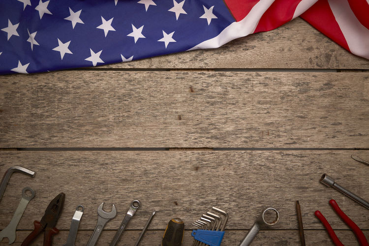 Directly above shot of american flag and work tools on wooden table