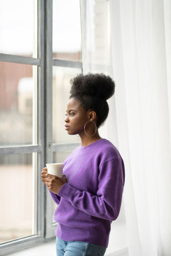 Thoughtful businesswoman with coffee cup looking through window