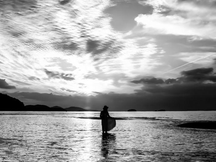 Silhouette person in sea against sky