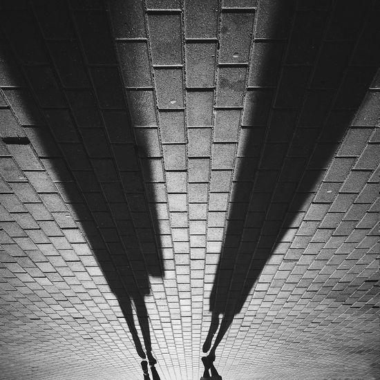 Shadows of people walking on road
