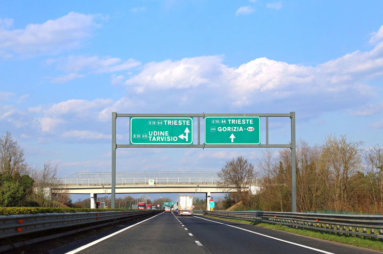 big road sign with directions to the city of Trieste and Udine in the large Italian motorway A4 Arrow E5 Italia Traffic Trieste Udine Autostrada Bivio Communication Crossroads Day Direction Freeway Guidance Highway Italy Motorway Palmanova Road Road Sign Road Signal Sky Text Transportation