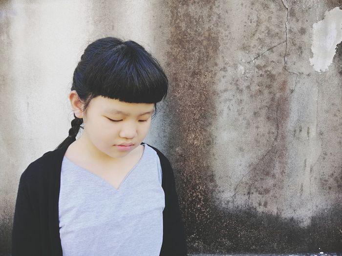 Girl looking at camera against wall