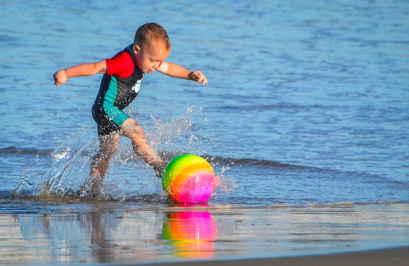 Boy kicking ball on shore at beach