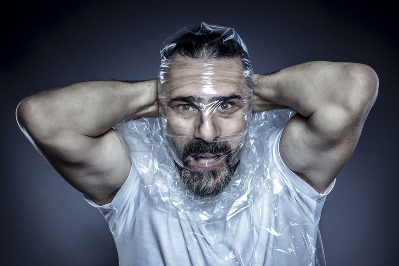 Portrait of man covering face with plastic against gray background