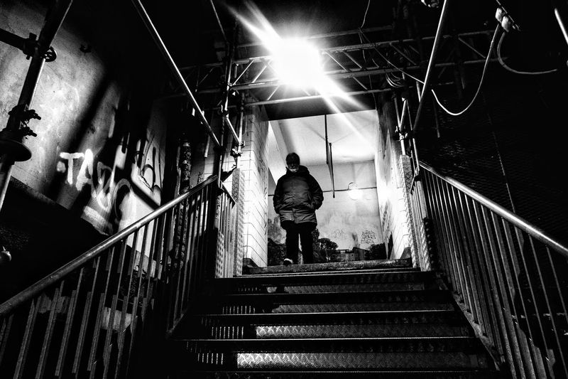 Rear view of man walking on staircase in illuminated building