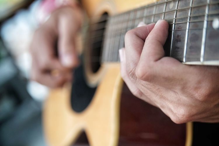 Close-up of hand playing the guitar