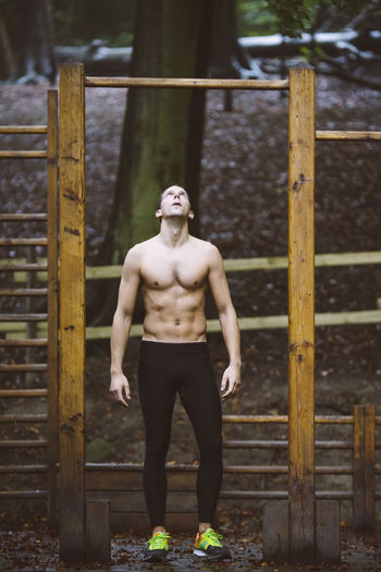 Full length portrait of shirtless man standing against brick wall