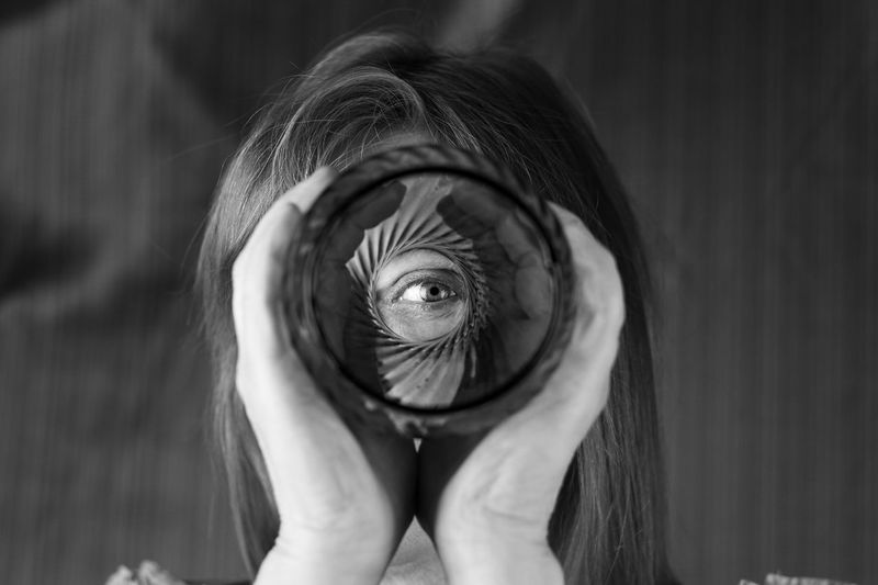 Close-Up Portrait Of Woman Looking Through Glass