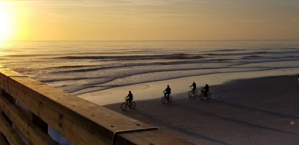 People riding bicycles on shore at beach during sunset