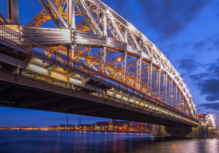 Low Angle View Of Illuminated Bridge Over River Against Sky