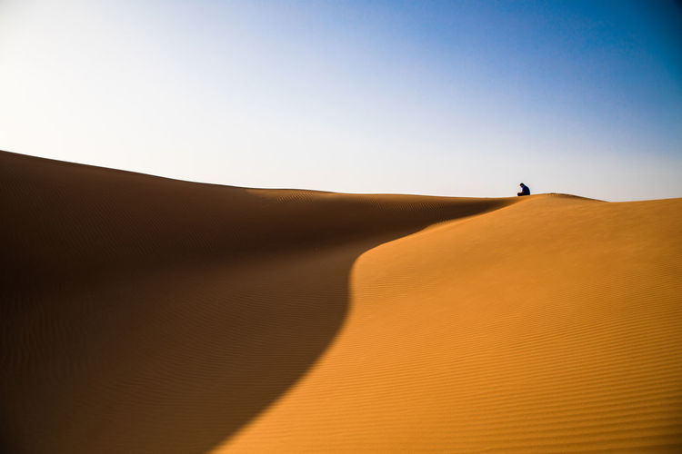 A man  on the dune in the desert