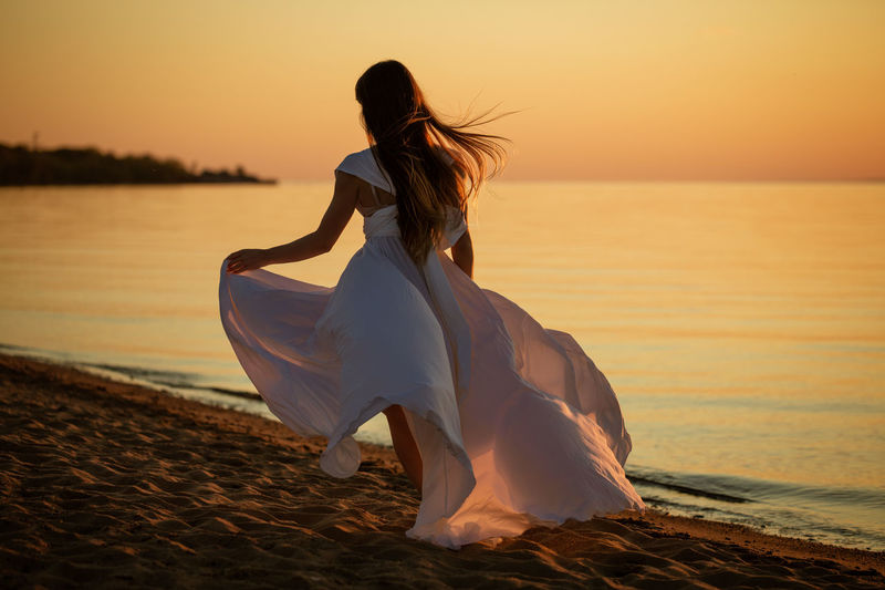 Young woman runs in a white dress on the seashore at sunset