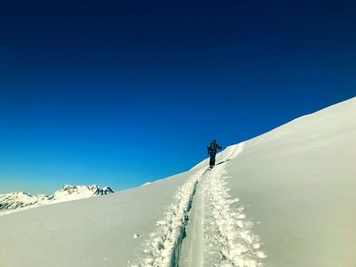 Walking Man Winter Snow Mountain Cold Temperature Sky Real People Clear Sky Winter Sport Leisure Activity Blue Adventure Sport Snowcapped Mountain Holiday One Person Nature Go Higher