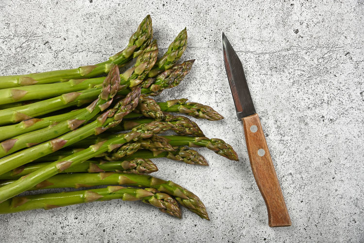Close up green asparagus shoots and knife on stone cooking cutting board Food And Drink Food Vegetable Green Color Freshness Healthy Eating Wellbeing Asparagus No People Still Life High Angle View Raw Food Indoors  Table Kitchen Knife Bunch Close-up Directly Above Vegan Vegan Food Vegetarian Food Copy Space Wood - Material Season  Cooking