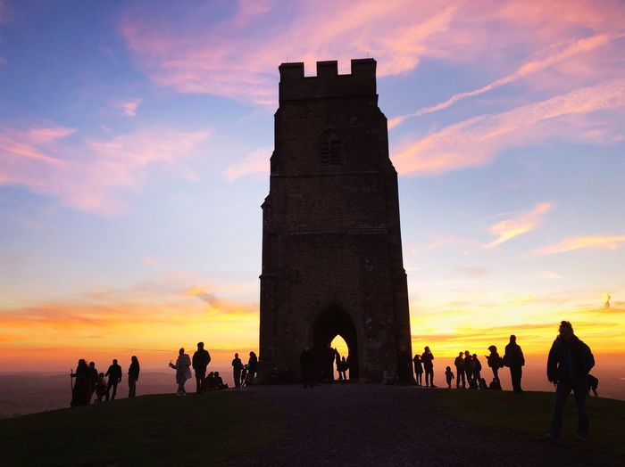 Glastonbury tor with tourists Glastonbury Beautiful Sunsets Sunset Full Moon Spirituality Spirituality Spirituality Sky Sunset Architecture Group Of People Real People Crowd Large Group Of People Men Travel The Past Women History Tourism Travel Destinations Cloud - Sky Building Exterior Orange Color Nature Built Structure Silhouette