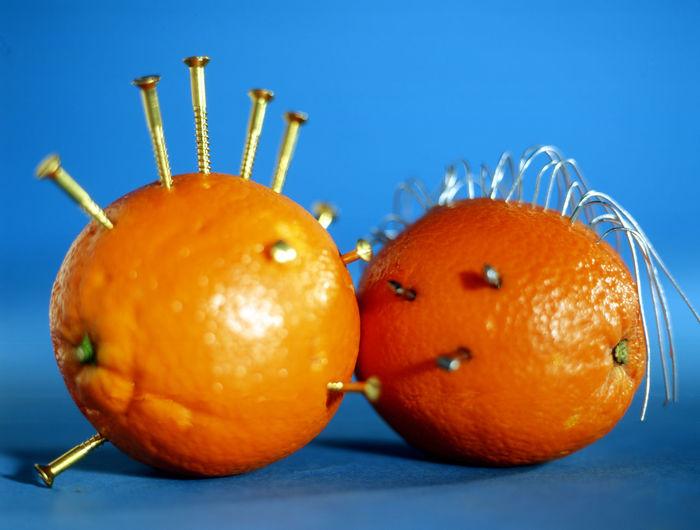 Close-Up Of Screws On Oranges Against Blue Background